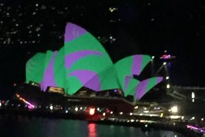 green and purple light on the sails of the Sydney opera House during Vivid