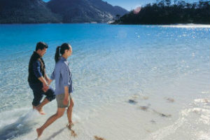 Couple walking in the water in Wineglass Bay