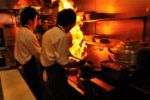 chefs cooking over a flaming wok