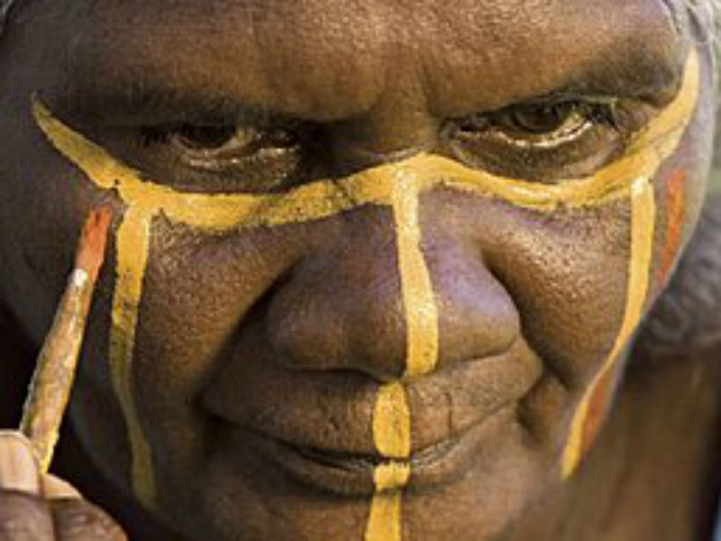 A traditional owner from the Tiwi Islands painting their face