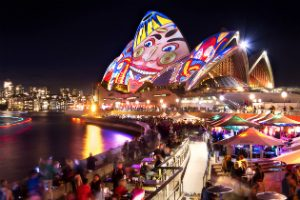 The sails of the Sydney Opera house painted with faces during Vivid