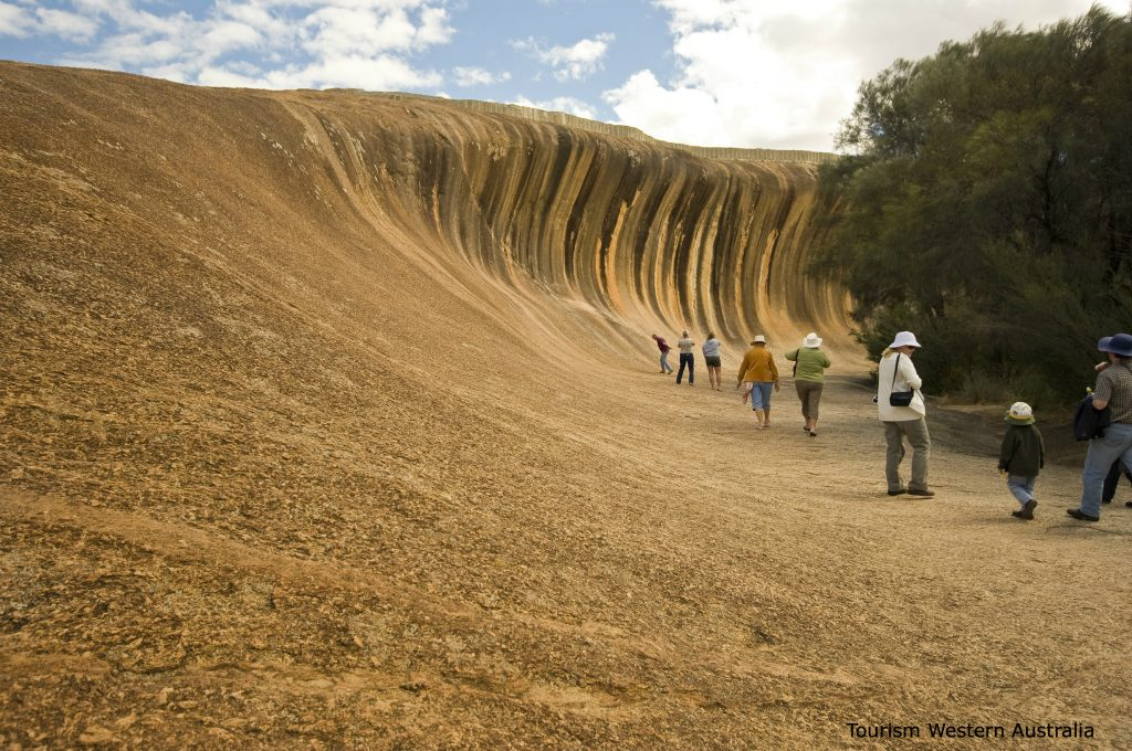 Image of Wave Rock with tourists  in the picture to show the size of it