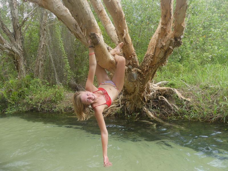 Paula wrapping her limbs around a tree hanging over Eli Creek