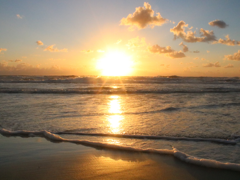 Standing on the beach watching the sunrise over the ocean